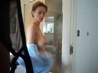 Busty brunette mom is in the shower washing and posing for cam
