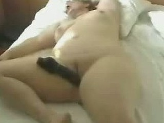 Fat pussy wants to be fucked. Excited plump girlie lies in bed and dude with camera shoves dildo inside her cunt.