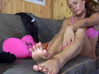 Doll-faced sweetheart relaxing on her beloved sofa and massaging her nyloned feet