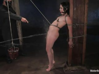 While this brunette with small titties and shaved pussy is tied up, the executor gives her a bucket of water on her body, the same bucket that was pulling the rope between her pussy lips. The ball gag she has and the dildo used on her cunt makes that bitch go crazy. Looks like she want some more, doesn't she?