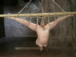 Sexy Kristina gets her pussy whipped while she is tied up to a metal bar with her legs spread and her head upside down. Her female executor enjoys punishing her unshaved cunt and spinning her by holding just her clit. She puts a vibrator on it and makes the slut moan with pleasure and begging her to cum!