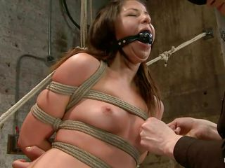With weights added to her big nipples, slutty milf Mia Gold is tied up and has one leg in the air for a better pussy domination. Having her mouth gagged, she can only moan. Her mistress sticks a big dildo in that wet cunt of hers and a vibrator on her clit to drive her crazy. Will she cum soon?
