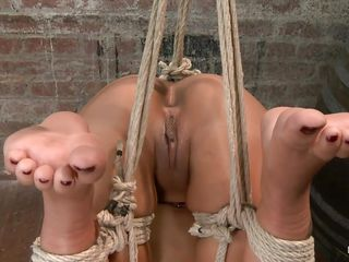 Skin Diamond is a ebony tattooed milf. As you can see, the gorgeous female is tied up with ropes, hanging on that ceiling. She must suffer for all the bad things she had done, and the guy makes sure. The black good looking babe enjoys getting punished while being bound on that table.